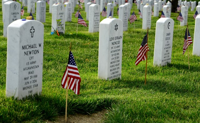 Old Guard Soldiers place flags at Arlington Cemetery