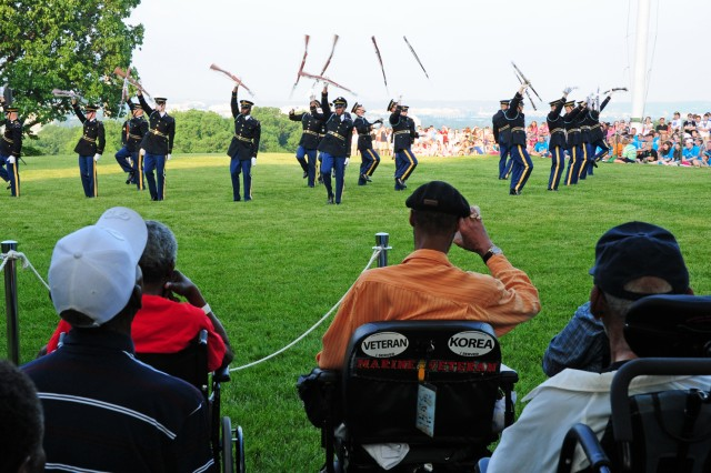 Korean War veterans watch the U.S. Army Drill Team perform at a special Salute from the Chief twilight tattoo, which honored five civilians for their contributions to Soldiers, veterans, wounded warriors and their families, at Joint Base Myer-Henderson Hall, Va., May 22, 2013.