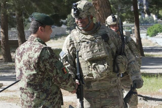 U.S. Army Maj. Demetrius Perry, a native of Houston, Texas, removes his glove prior to shaking hands with an Afghan National Army soldier during a visit to Forward Operating Base Naghlu Riverside, April 30, 2013. Perry emphasized to his soldiers the importance of building a strong rapport with their ANA counterparts. He is serves as senior adviser for Security Force Assistance Advisory Team 15, and assigned to the 4th Brigade Combat Team, 1st Cavalry Division, based out of Fort Hood, Texas. (U.S. Army photo by Staff Sgt. Richard Andrade, Task Force Long Knife Public Affairs)