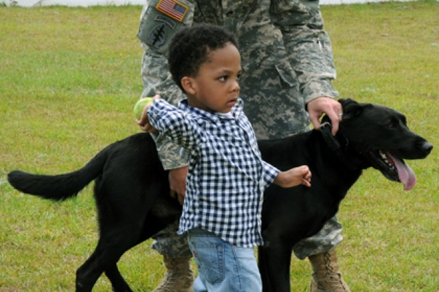 Staff Sgt. Craig Miller, 6th Military Police Det. Military Working Dog handler, holds on to Bo, Sgt. 1st Class Donald Tabb's MWD, as Tabb's nephew, Ukarrie, gets ready to throw a ball after the ceremony that named the Military Working Dog kennels after Tabb May 17.