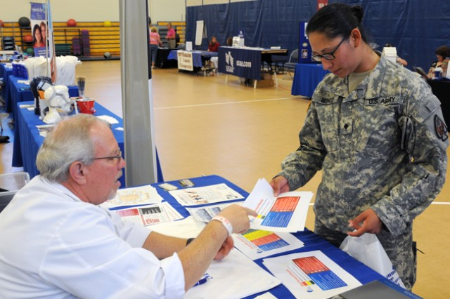 Spc. Valerie Munoz, Headquarters and Headquarters Company, 164th Theater Airfield Operations Group, listens to information provided by Southeast Alabama Regional Medical Center registered nurse Levonne Outlaw during the Fort Rucker Health Expo May 16.