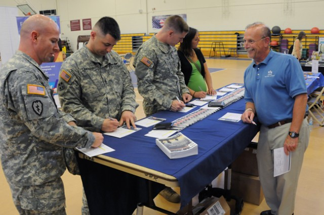 Chris Glennon (right), a United Services Automobile Association representative, speaks with Soldiers and Family members at the Fort Rucker Health Expo May 16.