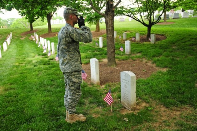 Spc. Brock Bowers, infantryman, Honor Guard Company, 3d U.S. Infantry Regiment (The Old Guard), renders honors to Medal of Honor recipient Sgt. Dwight H. Johnson after placing a flag on his grave during the Flags In event at Arlington National Cemetery.