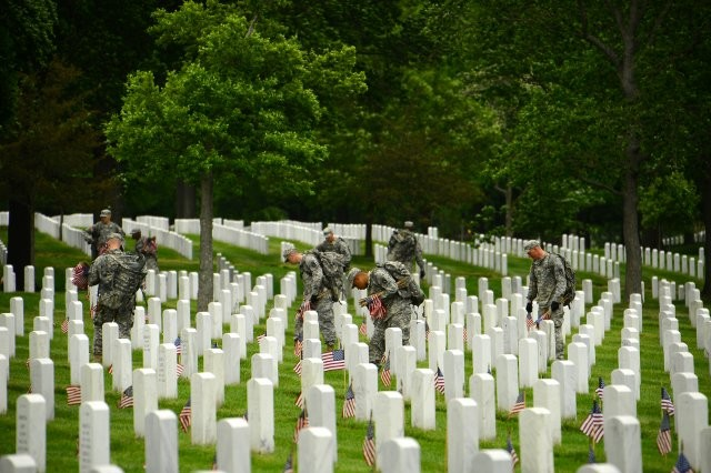 Old Guard Soldiers take care in placing an American flag in front of each grave at Arlington National Cemetery to honor the service and sacrifice of the nation's fallen service members.