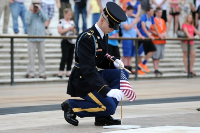 Spc. Seth Wymer, Sentinel, Tomb of the Unknowns, 3d U.S. Infantry Regiment (The Old Guard), places a flag at the foot of one of four crypts of the Unknowns in Arlington National Cemetery.