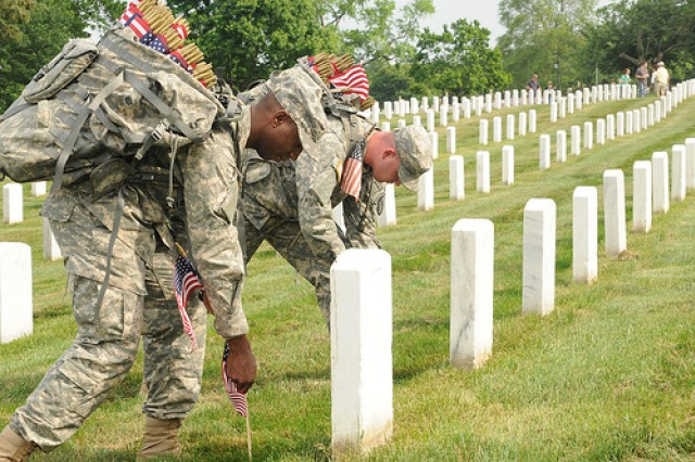 Old Guard Soldiers place flags at the graves at Arlington National Cemetery to honor the service and sacrifice of the nation's fallen service members.