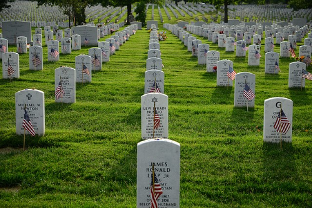 American flags, placed with care in front of gravestones, pay tribute to fallen service members at Arlington National Cemetery.