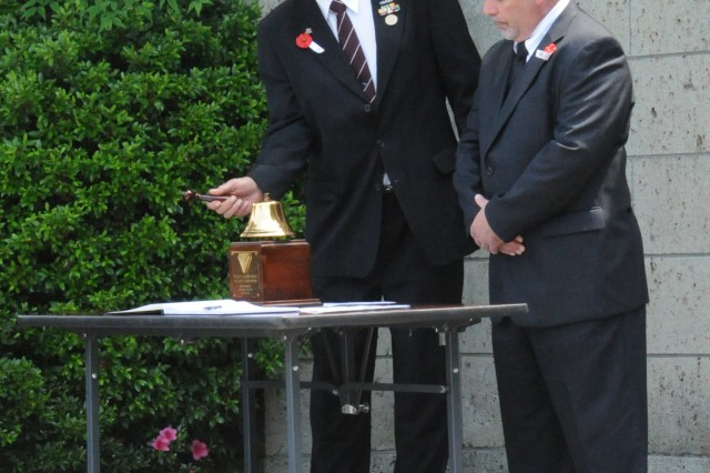 "VFW Post 1054 Commander Rick Farris and Jon Oliver, Fleet Reserve Association member, conduct the ""Two Bell"" ceremony during the Memorial Day ceremony on May 26 at the Yokohama War Cemetery in Hodogaya, Japan. The Two-Bell ceremony honors departed sailors and shipmates. (U.S. Army photo by Candateshia Pafford)"
