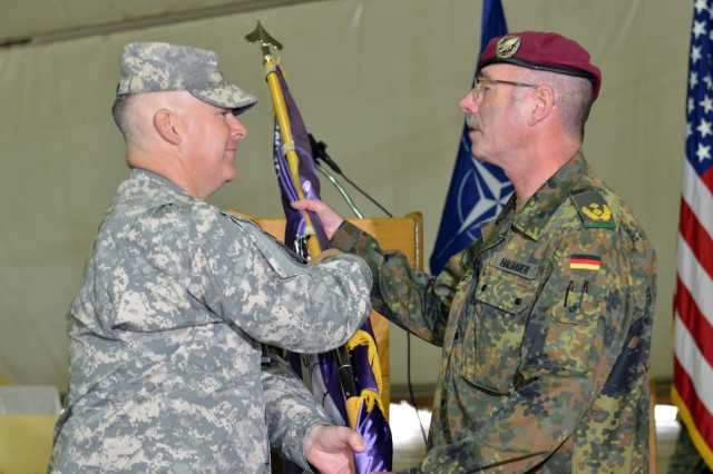 U.S. Army Lt. Col. Edward Cloyd, the outgoing commander of the Joint Readiness Detachment-East, passes the guidon to German Army Maj. Gen. Volker Halbauer, the Kosovo Forces commander, at the JRD-East transfer of authority ceremony at Camp Bondsteel, Kosovo, May 26. The passing of the guidon is an old tradition meant to symbolize the passing of responsibility from the outgoing commander to the incoming commander. (U.S. Army photo by Staff Sgt. Cody Harding, 4th Public Affairs Detachment)