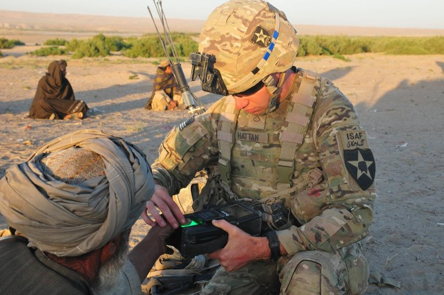 """Pfc. Tyler Hattan, an infantryman with Company C """"Chaos"""", 1st Battalion, 38th Infantry Regiment, Combined Task Force 4-2 obtains the fingerprints of a local Afghan near the Kheybari Ghar ridgeline in the Panjwa'i District of Afghanistan using the Secure Electronic Enrollment Kit II (SEEK) May 2 as a part of """"Operation Rising Sun III."""" The company partnered with Weapons Company, 6th Kandak, 205th Afghan National Army or the last company-sized operation of C Company's nine-month deployment in support of Operation Enduring Freedom. (U.S. Army photo by Sgt. Kimberly Hackbarth, 4th SBCT, 2nd Inf. Div. Public Affairs Office)"""