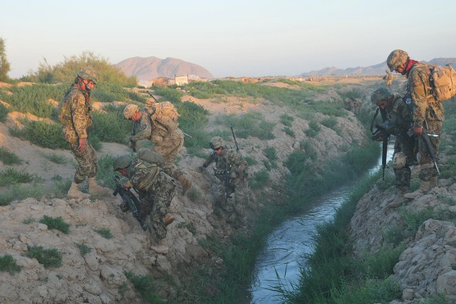 "Soldiers of Company C ""Chaos"", 1st Battalion, 38th Infantry Regiment, Combined Task Force 4-2 and Weapons Company, 6th Kandak, 205th Afghan National Army cross a canal near the Kheybari Ghar ridgeline in the Panjwa'i District of Afghanistan as part of ""Operation Rising Sun III"" May 2.  The joint team traversed more than 32 kilometers of terrain while searching 82 Kuchi camps and 12 structures of interest. (U.S. Army photo by Sgt. Kimberly Hackbarth, 4th SBCT, 2nd Inf. Div. Public Affairs Office)"