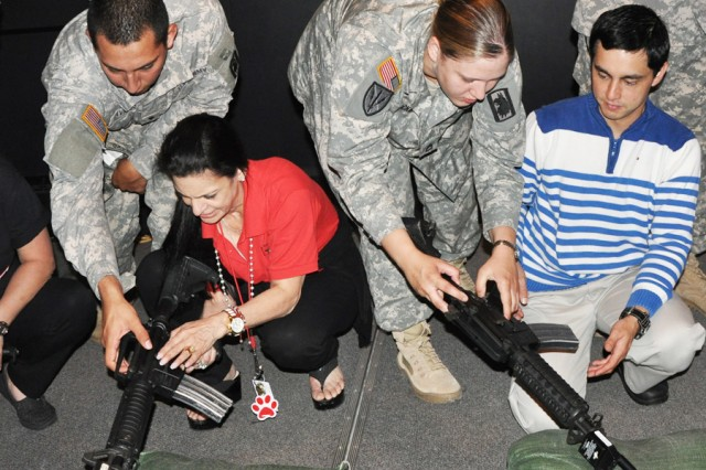 Spc. Elijah Cavazos and Sgt. 1st Class Sandra Hocking of the 470th Military Intelligence Brigade show two teachers from Bowden Elementary School how to release the bolt on an M4 rifle. The Engagement Skills Trainer 2000 at Joint Base San Antonio-Fort Sam Houston allowed school staff and teachers to experience firing the weapon in a realistic simulation May 9 as a team-building event. (U.S. Army photo by Spc. Sammy Rosado)