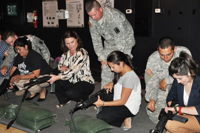 Soldiers of the 470th Military Intelligence Brigade help Bowden Elementary School teachers and staff prepare to engage in simulated M14 rifle shooting. The team-building event took place in the Engagement Skills Trainer 2000 at Joint Base San Antonio-Fort Sam Houston May 9. (U.S. Army photo by Spc. Sammy Rosado)