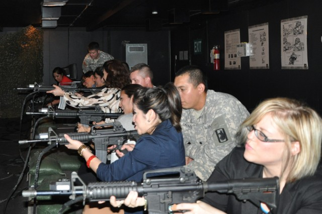 Elementary school staff and teachers receive some pointers from 470th Military Intelligence Brigade Soldiers as they prepare to open simulated M4 rifle fire at simulated enemy Soldiers. The team-building event took place in the Engagement Skills Trainer 2000 at Joint Base San Antonio-Fort Sam Houston May 9. (U.S. Army photo by Spc. Sammy Rosado)