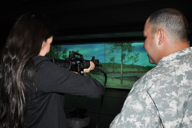 A Bowden Elementary School teacher watches for a simulated enemy soldier to emerge from the simulated terrain while a real Soldier of the 470th Military Intelligence Brigade watches her. School staff and teachers took part in a team-building event at the Engagement Skills Trainer 2000 at Joint Base San Antonio-Fort Sam Houston May 9. (U.S. Army photo by Spc. Sammy Rosado)