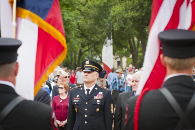 Sgt. Maj. of the Army Raymond F. Chandler III stands at attention as the service flags for each branch of the military are raised at the beginning of the Memorial Day ceremony at the Georgetown-Williamson County, Texas, Veterans Memorial Plaza, May 27, 2013. Veterans from every conflict since World War II were in attendance.