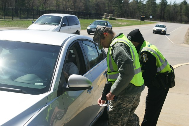 Spc. Louis Meservy (left) of the 438th Military Police Detachment of Salt Lake City and Fort McCoy police officer Julius Dumale perform a gate access check at Fort McCoy's Main Gate. The 438th supported the Directorate of Emergency Services Police Department during its May training at Fort McCoy.