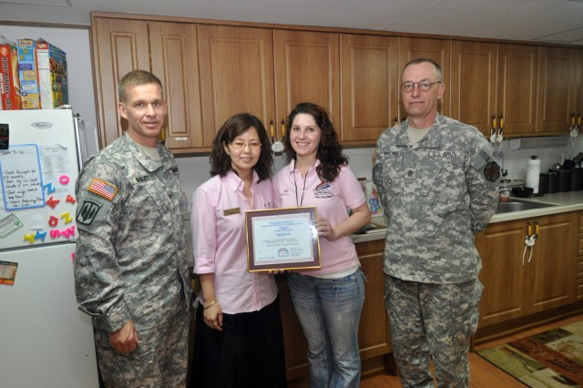 Col. Michael E. Masley, garrison commander at USAG Yongsan, symbolically approved the opening of a Hannam Village home-based Family Child Care by presenting an official certificate to Michelle Pritchett, a Family Child Care provider in Hannam Village, May. 28. (U.S. Army photo by Sgt. Lee Hyokang)