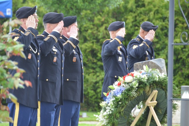 From left, Command Sgt. Maj. Michael Clowser, Chief Warrant Officer 5 Tom Walton and Col. Jay Voorhees of the 12th Combat Aviation Brigade Col. Kelly J. Lawler and Command Sgt. Maj. Leeford C. Cain, the U.S. Army Garrison Ansbach command team, salute at the conclusion of a Memorial Day ceremony at the Memorial Garden beside the 12th CAB headquarters at Katterbach, Germany, May 29.