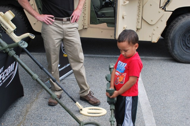 A young visitor who stopped by SEDD's booth during the APG Armed Forces Day event wanted to demonstrate to Brendan Patton, SEDD, how he could handle the hand held metal detector on his own.