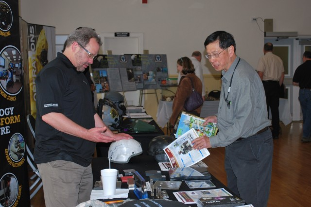 Steve Taulbee, WMRD, speaks about advanced armor materials to a visitor at the APG Armed Forces Day.