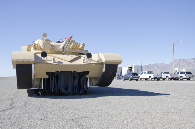 Engineers push a tank target onto the runway during a systems check at Condron Army Airfield on White Sands Missile Range, N.M. The tank is made of the same plastic board used for political campaign signs, and fitted with metal strips and heaters to make it appear like a real tank on various sensors.