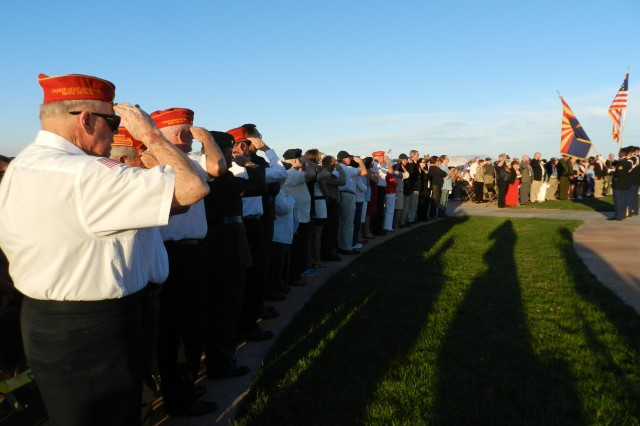 Members of the audience at the Memorial Day service at Southern Arizona Veterans Memorial Cemetery stand and salute during the retiring of the colors on Monday. The ceremony was hosted by Thunder Mountain Detachment 1283 of the Marine Corps League, whose veterans occupied the front row along with other honored dignitaries.