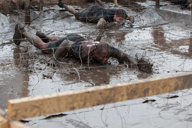 Command Sgt. Maj. James Kilpatrick, Command Sergeant Major of the 1-345th Engineer Battalion, First Army Division East, tackles the electro-shock low crawl obstacle at the Tough Mudder 2013 competition in Seneca, Ill.  Several Soldiers and family members from the 157th Infantry Brigade celebrated the Armed Force weekend participating in this unique competition. (U.S. Army photo by Maj. Penny Zamora)
