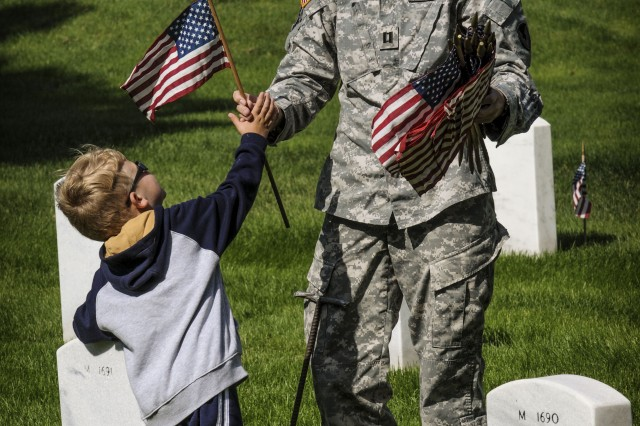 Capt. Tera Lerch passes a flag to her son for placement at a headstone in the Rock Island Arsenal National Cemetery on Rock Island Arsenal, Ill., May 23, in preparation for the Memorial Day Ceremony.  (Photo by Sgt. 1st Class Sean Riley, ASC Public Affairs)