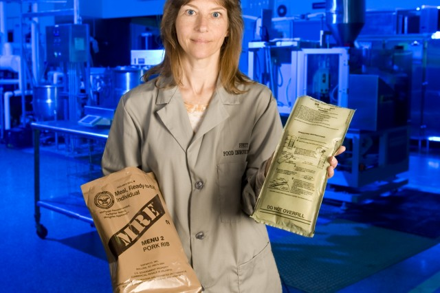 Lauren Oleksyk of the Natick Soldier Research, Development and Engineering Center's Department of Defense Combat Feeding Directorate, holds a Flameless Ration Heater and a Meal, Ready-to-Eat. This is the 20th anniversary of the heater's introduction.