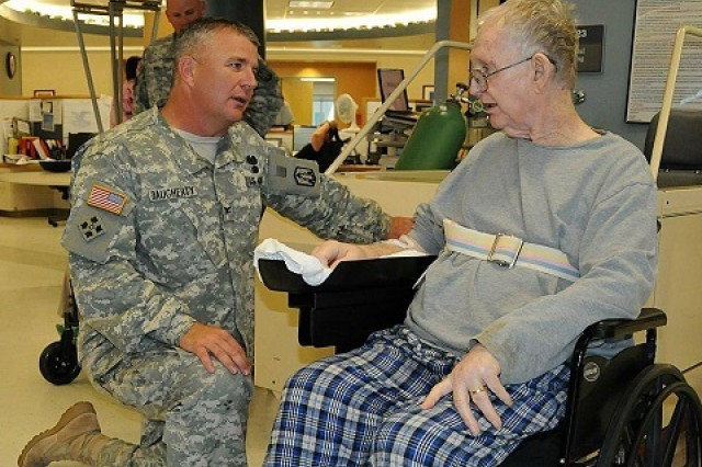 Col. Timothy Daugherty, 214th Fires Brigade commander, talks to a patient at the Jack. C. Montgomery Veterans Affairs medical hospital. Daugherty saidtrips to the VA to hang out and talk with veteran patients is a great way to support the troops.