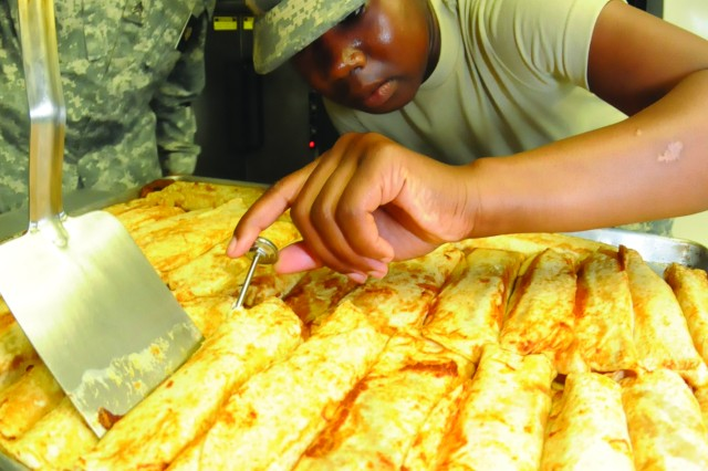 Pfc. Devita Bone uses a thermometer to measure the temperature of the enchiladas her team cooked up for the lunchtime meal. Bone and the other food service Soldiers prepare roughly eight meals for their peers during 40 hours of instruction at the Field Operations Training Branch.