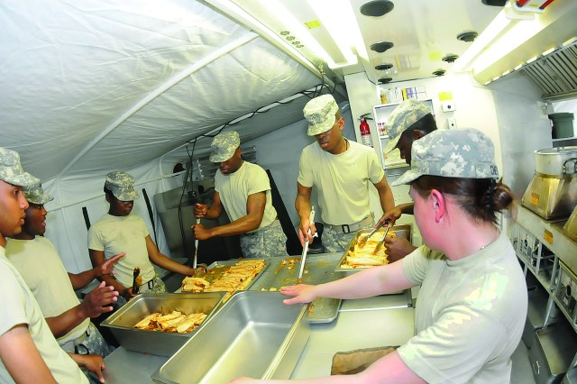 Seven Soldiers pitch in to help prepare enchilada entrees during hands-on training May 23 at the Field Operations Training Branch of the Joint Culinary Center of Excellence, Quartermaster School.  The Soldiers undergo 40 hours of instruction, learning how to setup mobile cooking facilities and preparing meals in them.  They also learn about sanitation practices.