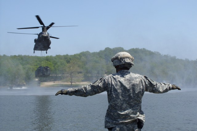 Sgt. Christopher Pena, a bridge crew chief assigned to 50th Multi-Role Bridging Company, 5th Engineer Battalion, signals for a helicopter hover during a sling load operation May 15, 2013, at Lake of the Ozarks Recreation Area. The 50th MRBC is one of five active-duty bridging companies in the U.S. Army.