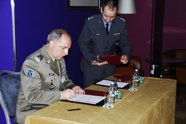 WARSAW, Poland - Brig. Gen. Jan Dziedzic, the chief of Logistics Planning Directorate Polish Army, signs letters of invitation for Latvia, Lithuania, and Estonia to join the National Territorial Commanders Committee, May 29. Lt. Col. Pawel Kwarto, senior host nation support specialist, Logistics Directorate, Polish Armed Forces general staff, assists Dziedzic. The three-day event's focus was to develop a data base to capture host nation support of best practices of its members in support of International Security Assistance Force/Operation Enduring Freedom, to create an action plan to strengthen interagency coordination to more efficiently respond to civil emergencies, and discuss membership expansion.