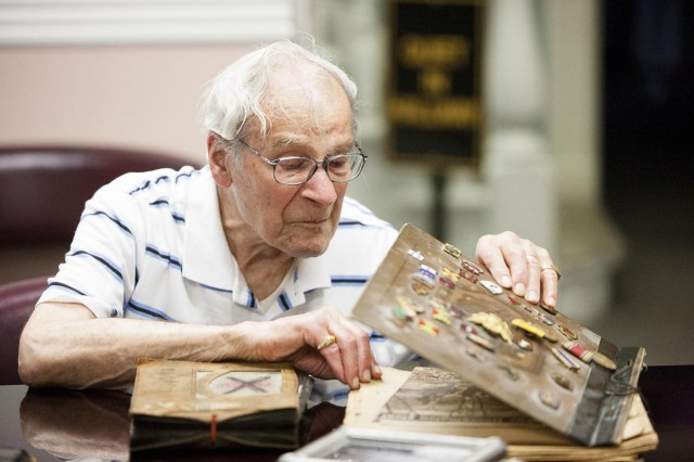 "Anthony ""Tony"" Vernille, 95, looks through scrapbooks he brought to Joint Base Myer-Henderson Hall May 22, 2013. Vernille was stationed on pre-World War II Fort Myer."