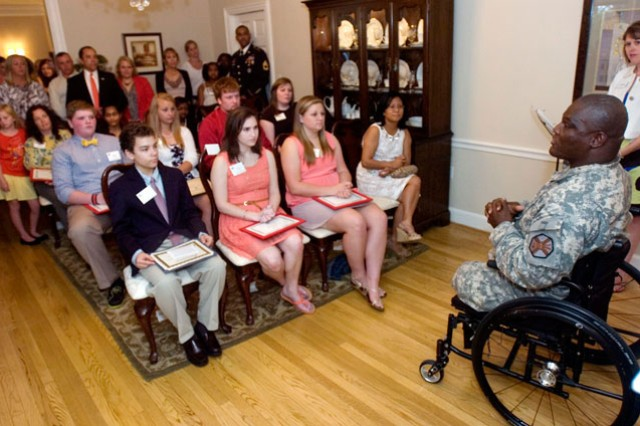 The Belvoir Spouses' Clubs 2013 Scholarship Award recipients (front row: Anthony Applewhite, left, Alexandra Georgi Cassandra Buer. Second row: Benjamin Hodges, left, Summer Scott, Benjamin Canady, Chelsi Strange.  Back row: Dawn Cook, left, Sheeka Sharma, Kiont Newsome) listen to Fort Belvoir Garrison Commander Col. Gregory D. Gadson at the historic Quarters One at Fort Belvoir May 22.