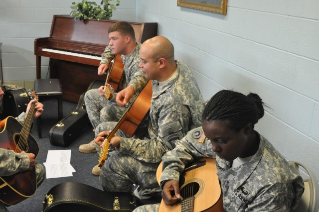 Specialist Gerrick Cole, Sgt. Michael Harris and Lt. Col. Zabrina Seaymaynard, practice the theory of guitar in an intermediate provided by the Sounds of Acoustic Recovery program at the Dale Wayrynen Recreation Center May 16.  SOAR is an eight-week program that allows wounded Soldiers to learn the basics of guitar, piano or receive voice lessons at a beginner or intermediate level. SOAR provides therapy to help Soldiers remain strong and recover from injuries as they enter the next phase of their lives.
