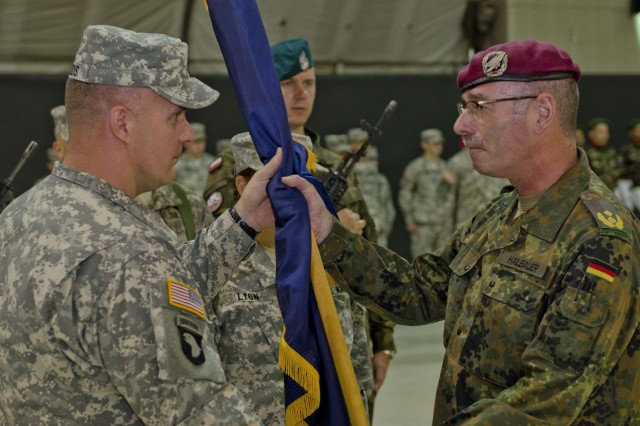 German Army Maj. Gen. Volker Halbauer, the commander of Kosovo Forces, presents the guidon to U.S. Army Col. David J. Woods, native of Denbo, Pa., the commander of the 525th Battlefield Surveillance Brigade and the incoming commander of the Multinational Battle Group-East, during a transfer of authority ceremony at Camp Bondsteel, June 1. (U.S. Army Photo by Spc. Samantha Parks, 4th Public Affairs Detachment)