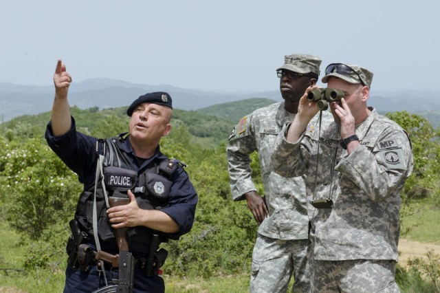 Police Officer Guzmend Jakupi, a member of the Kosovo Border Patrol, shows U.S. Army Capt. Anthony Wilkins and Chief Warrant Officer Two Andre Harris, members of the KFOR 17 Joint Law Enforcement Liaison Team, a distant route used by smugglers during a dismounted patrol along the Administrative Boundary Line, May 29. The ABL serves as a dividing line between Kosovo and Serbia, and both sides patrol the ABL to stop smugglers from crossing the boundary illegally. (Photo by Staff Sgt. Cody Harding, 4th Public Affairs Detachment)