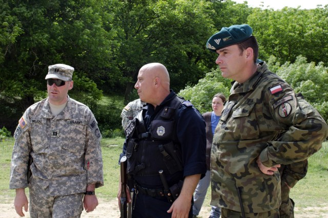 U.S. Army Capt. Anthony Wilkins, a member of the Kosovo Forces 17 Joint Law Enforcement Liaison Team, speaks with Guzmend Jakupi, a Kosovo Border Patrolman, and Polish Army Sgt. Tomash Wierzejeuski, a member of the Polish Coy, near an Administrative Boundary Line crossing point in Kosovo, May 29. (Photo by Staff Sgt. Cody Harding, 4th Public Affairs Detachment)