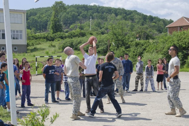 U.S. Army soldiers with Liaison Monitoring Team 4 play a game of three-on-three basketball with school children at the Kenan Halimi School May 30. Troops were invited for a field day by the school director. (U.S. Army photo by Spc. Samantha Parks, 4th Public Affairs Detachment)