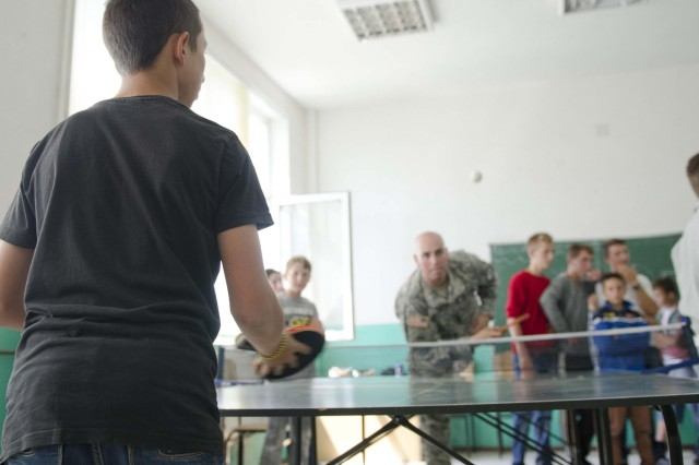 A school child at Kenan Halimi School competes in a pingpong game against Spc. Stanley Walker, Liaison Monitoring Team 4 and native of Brentwood, N.Y., during a field day May 30. Walker said the children went easy on him since it was his first time playing the game. (U.S. Army photo by Spc. Samantha Parks, 4th Public Affairs Detachment)