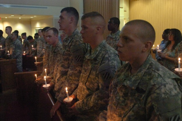 U.S. Army Pfc Cory Tallman, Spc. Jacob Baker and Spc. Brian Pierce, with other Soldiers from Bravo Company, 1st Battalion, 64th Armor Regiment, 2nd Brigade Combat Team, stand with lit candles  at the Survivor Outreach services candlelight vigil, to honor family members of fallen soldiers, at the main post chapel, Fort Stewart, Ga., May 23, 2013.  (U.S. Army photo by Staff Sgt. Roger RyDell Daniels/Released)