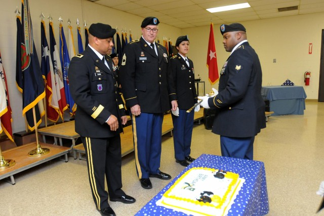 """Spc. Necory Smith presents a saber to Brig. Gen. Gracus K. Dunn, commanding general of the 85th Support Command, for the cake-cutting portion of the 238th Army birthday celebration at the unit's headquarters. Dunn then passed the saber to retired Master Sgt. Michael Kreinbring, who was honored as the """"most senior"""" noncommissioned officer to participate in the cake cutting. Pfc. Yvette Leon also participated in the cake cutting as the """"most junior"""" Soldier of the unit. Following the cake cutting, the unit sang """"The Birthday Song,"""" accompanied by a brass ensemble from the 85th Army Band, 88th Regional Support Command."""
