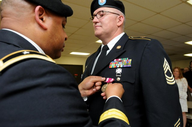 Master Sgt. Michael Kreinbring, assigned to the 85th Support Command, is presented the Meritorious Service medal by Brig. Gen. Gracus K. Dunn, commanding general of the 85th Support Command and deputy-commanding general of First Army Division West, during Kreinbring's retirement ceremony at Arlington Heights, Ill, June 1, 2013.