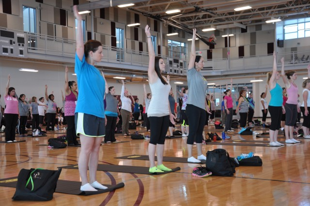 FORT CARSON, Colo. -- About 130 military spouses participate in a yoga session at Iron Horse Sports and Fitness Center May 22, to kickoff the 2013 Mountain Post Spouse Wellness Conference. The event featured four 45-minute breakout sessions, including a health fair, rock climbing and Zumba.
