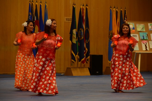 Three members of Paradise Blend, a group at U.S. Army Garrison Hohenfels that celebrates Asian-American and Pacific Islander culture, perform a Filipino candle dance during 412th Aviation Support Battalion and U.S. Army Garrison Ansbach's Asian-American and Pacific Islander Heritage Month observance May 31.