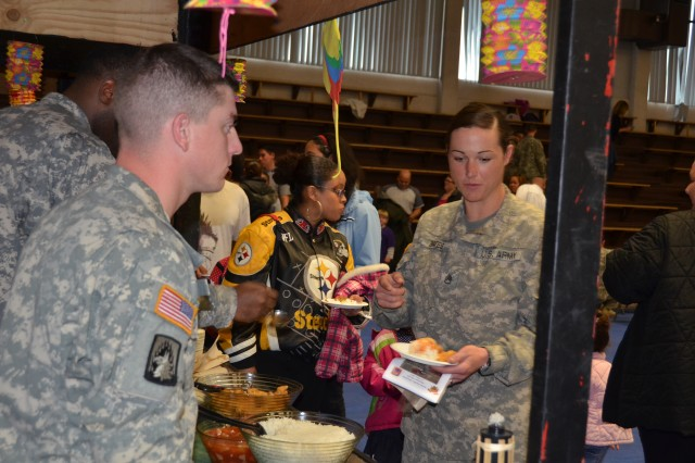 Staff Sgt. Katie Bates, right, B Company, 412th Aviation Support Battalion, samples various Asian American and Pacific Islander cuisine at 412th Aviation Support Battalion and U.S. Army Garrison Ansbach's Asian-American and Pacific Islander Heritage Month observance May 31.