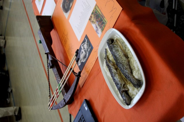 A student displays a crossbow and a typical meal at the Time Traveler Fest at Vilseck High School, May 30.